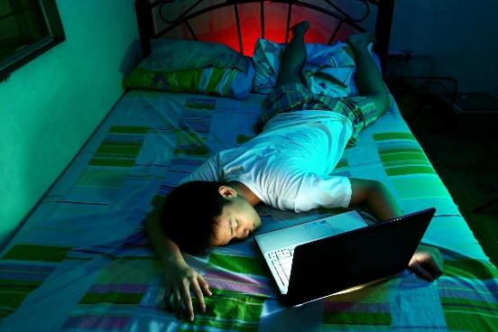 Un adolescent dort sur son lit, devant un ordinateur portable