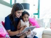 Une mère et sa fille jouent sur une tablette électronique ensemble