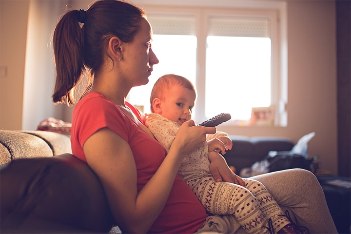 A woman with a baby on her lap holding a remote control, watching television