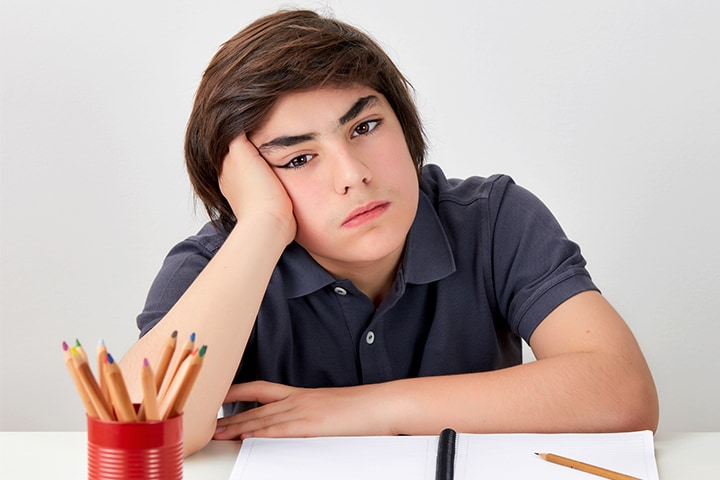 A frustrated and bored male teen trying to get some homework done
