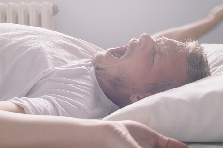 A man yawns and stretches in bed