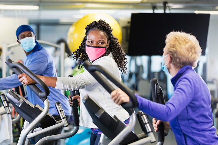 A multi-ethnic group of three people working out at the gym, on elliptical cross trainers, wearing protective face masks