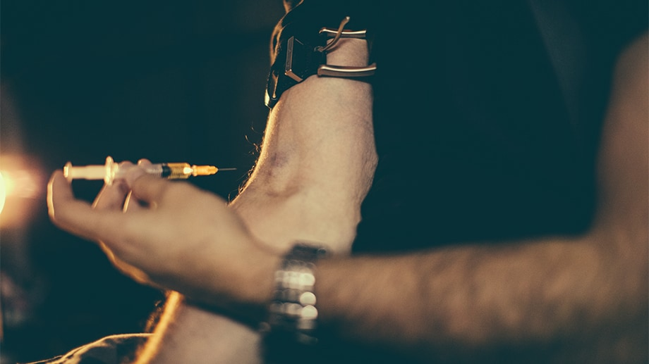 A man injecting drugs into his arm