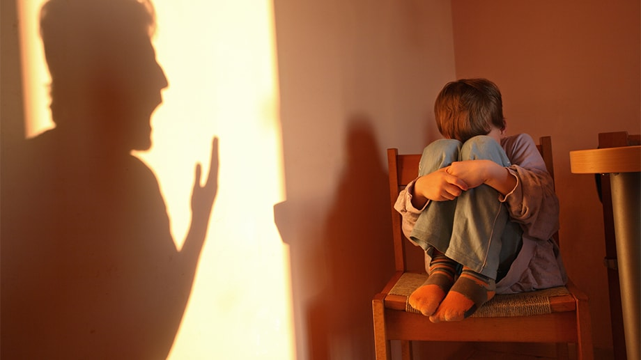 A young boy cowers on a chair next to a shadow silhouette of a man yelling and gesticulating.