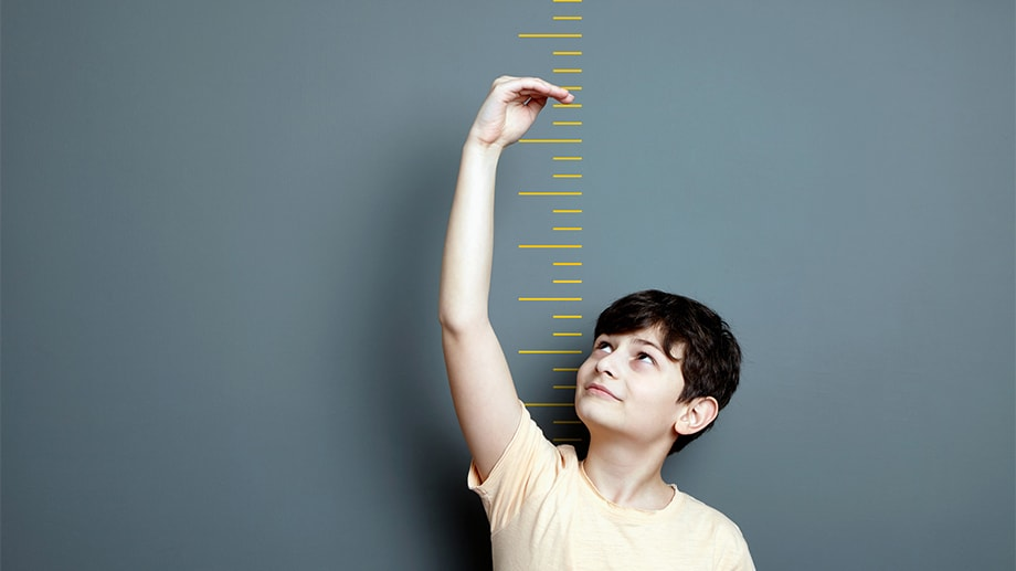 A young boy stands in front of a wall with height measurement marks and has his hand up to show how tall he'd like to be