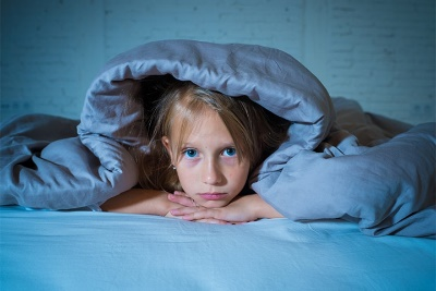 A young girl with insomnia in bed under a blanket with her chin resting on her hands