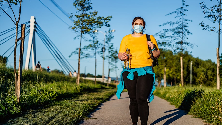 A young overweight woman wearing a protective face mask and workout gear on her way to training in a public park.