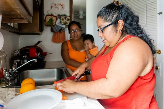 An obese Mexican-American woman making fruit salad in the kitchen as another woman and child look on.