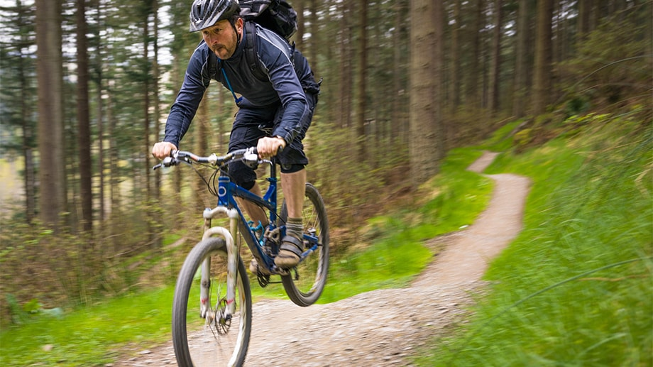 A man does a jump on his mountain bike in the woods