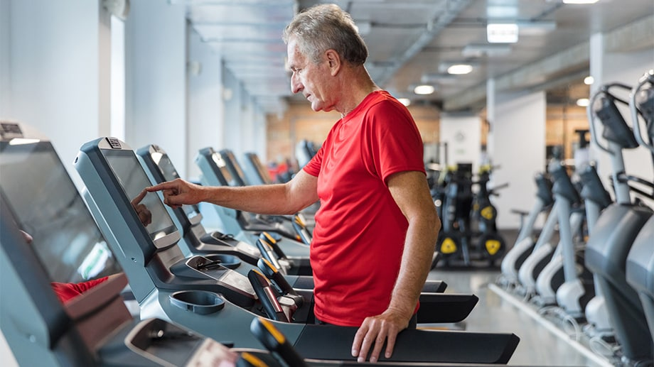 A mature man enters his walking program into a treadmill at a gym