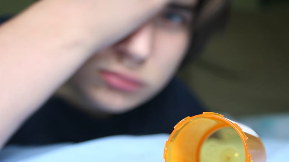 A young male teen laying on his bed near an empty prescription bottle