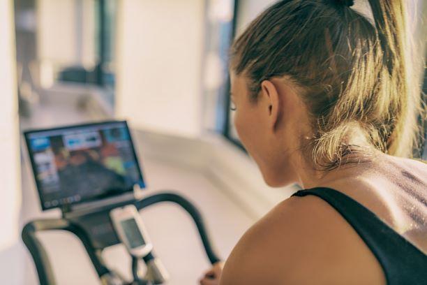 Female athlete training on peloton.