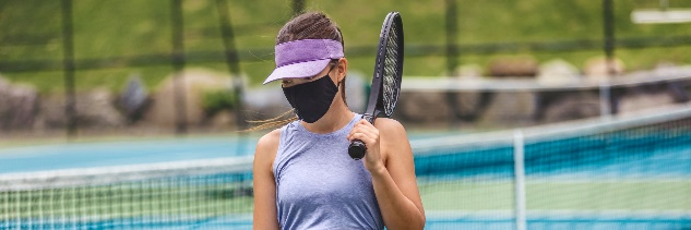 Woman wearing mask with tennis racquet over her shoulder.