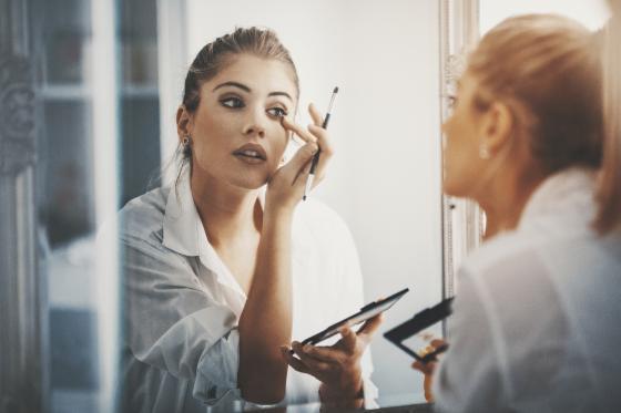 Une femme se maquille dans une salle de bain