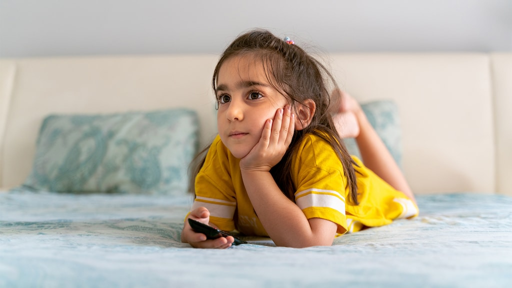A little girl lays on her parents bed holding a remote and watching television.