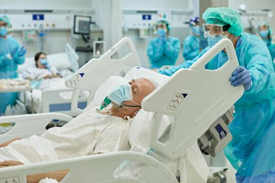 Du personnel soignant déplace un patient COVID à l'hôpital