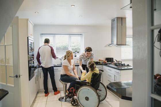 Un jeune souffrant de sclérose latérale amyotrophique dans une cuisine entouré de sa famille