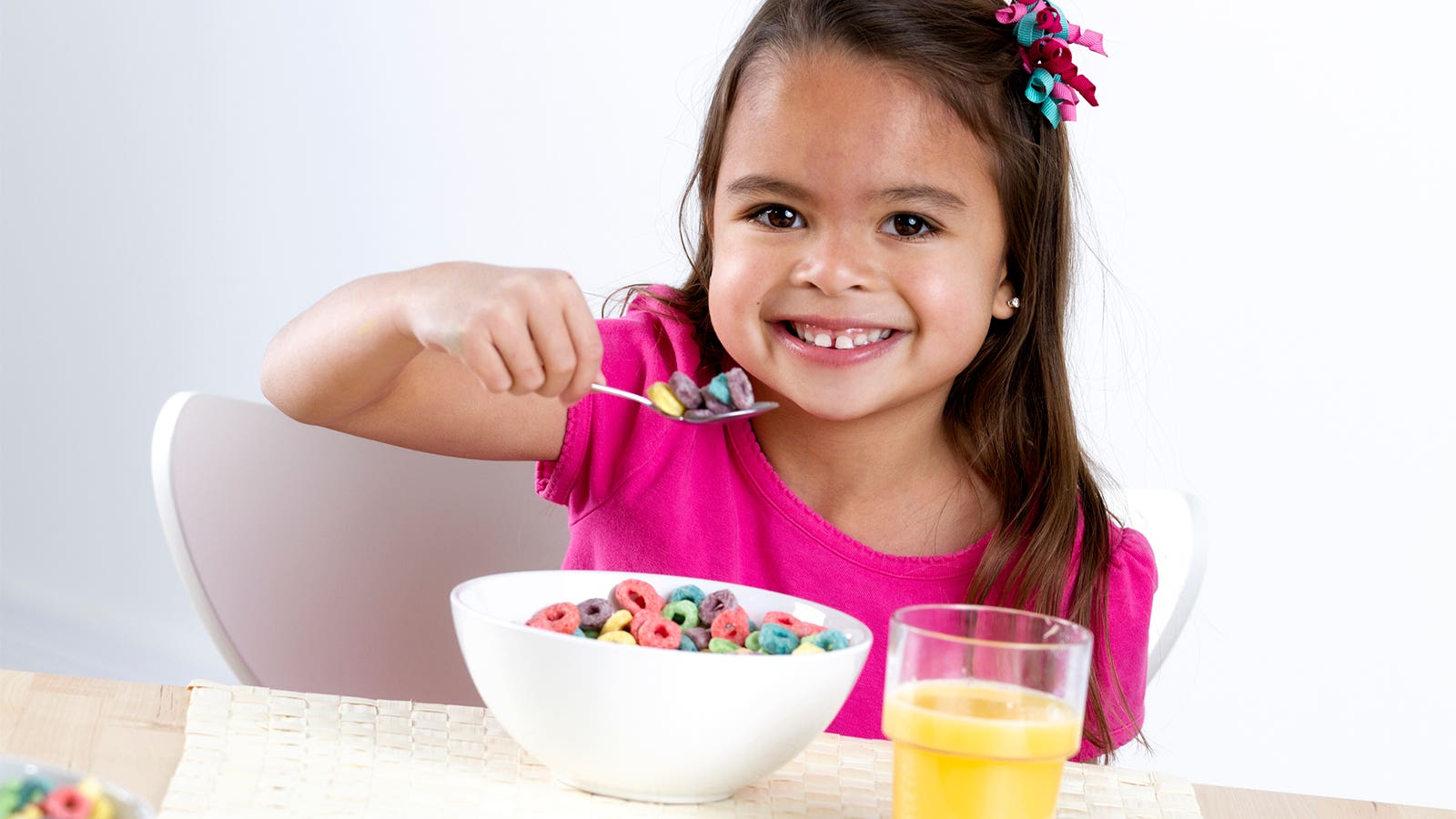 A little girl eats Fruit Loops cereal.