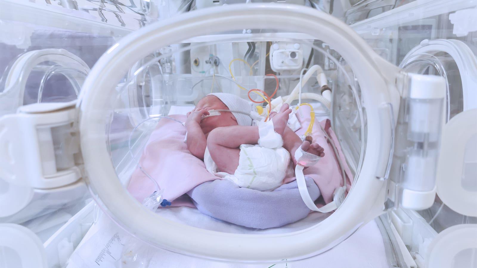 A preterm infant in an incubator in the neonatal ICU.