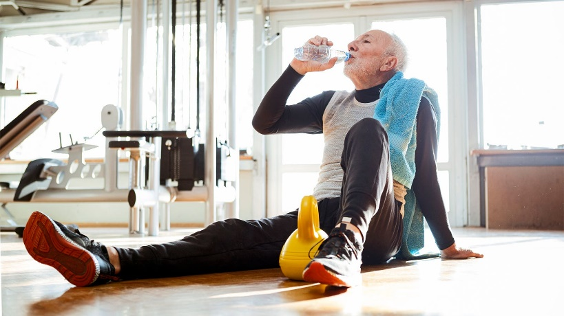 A senior man sits on the floor with a kettle bell in a gym and drinks from a water bottle.