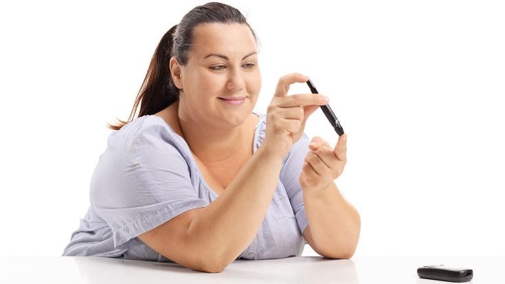 An overweight woman checks her blood sugar.