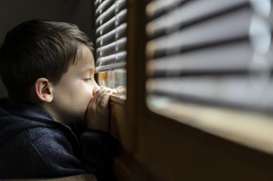 un enfant déprimé regarde à travers la fenêtre