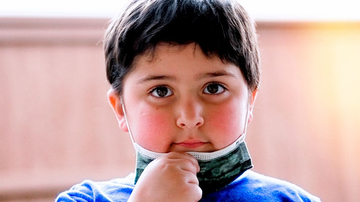 A chubby young boy lowers his protective mask.