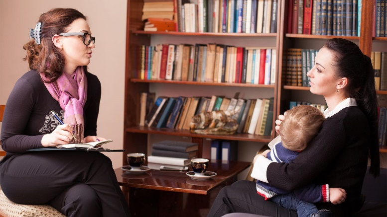 A female therapist visits a mother and her infant at home.