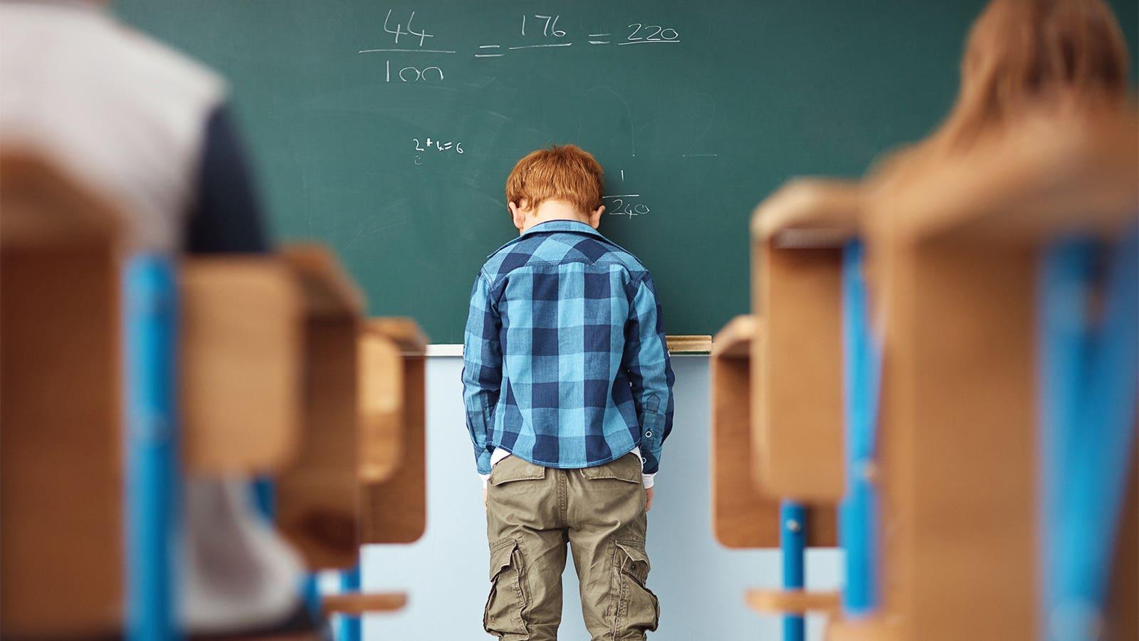 A young boy with his head on the blackboard at the front of a classroom.