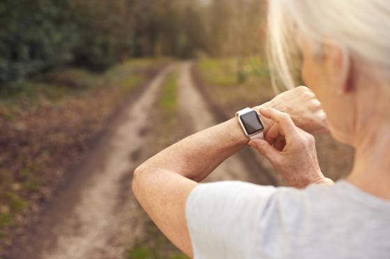 Une dame regarde sa montre intelligente en marchant