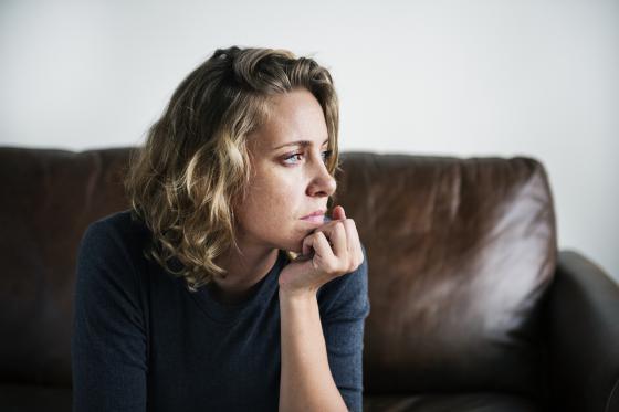 une femme anxieuse réfléchit sur son divan