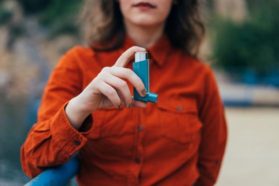 une femme asthmatique tient son inhalateur
