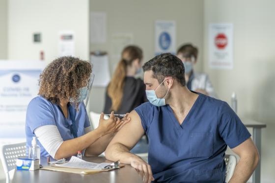 une infirmière vaccine un travailleur de la santé contre la COVID